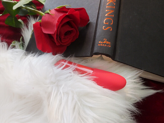 The Tango X in white faux fur, with a rose and an open black and red book